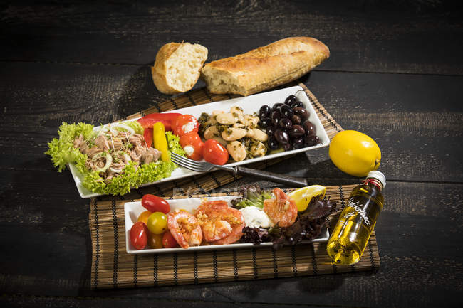 Антипасти, тунец, салат, заполненная паприкой, белая фасоль, черная оливка, креветки, сметана, помидоры и белый хлеб — стоковое фото