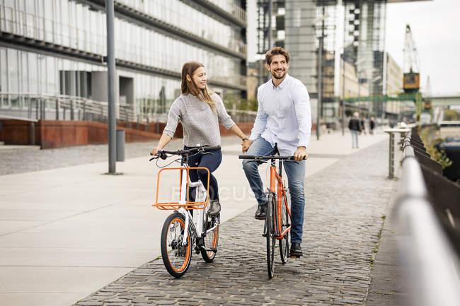 Couple souriant à vélo dans la ville — Photo de stock