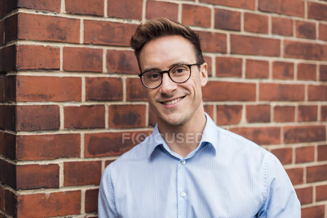 Portrait of smiling young businessman at brick wall — Stock Photo