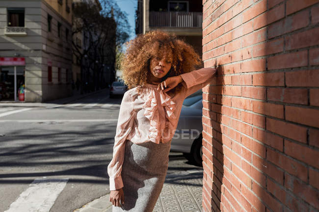 Portrait of beautiful young woman with afro hairdo leaning against brick wall in the city — Stock Photo