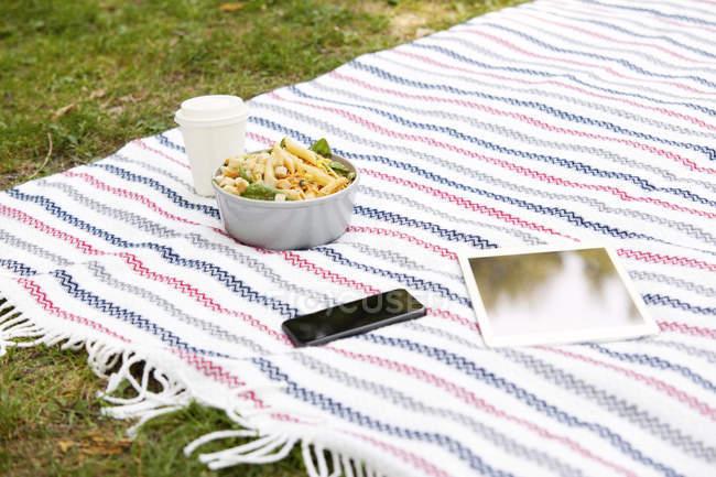 Стільниковий телефон, планшет, кава піти і миску локшини салат на ковдру в парку — стокове фото