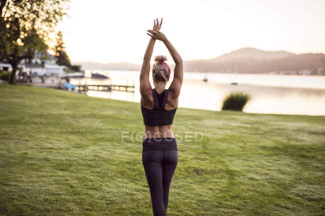 Женщина в спортивной одежде, стоящая на лугу и простирающаяся возле озера — стоковое фото