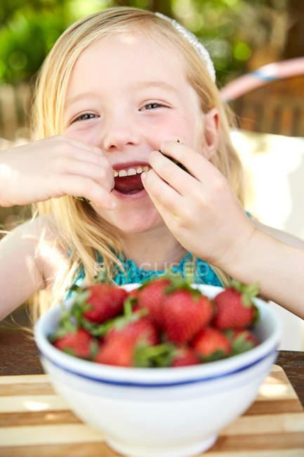 Portrait of happy girl eating strawberries — Stock Photo