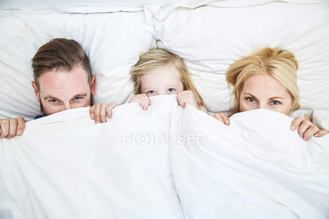 Portrait of family lying in bed and hiding under blanket — стоковое фото