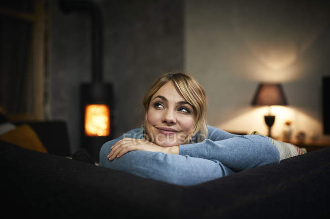 Portrait of smiling woman relaxing on couch at home in evening — Stock Photo