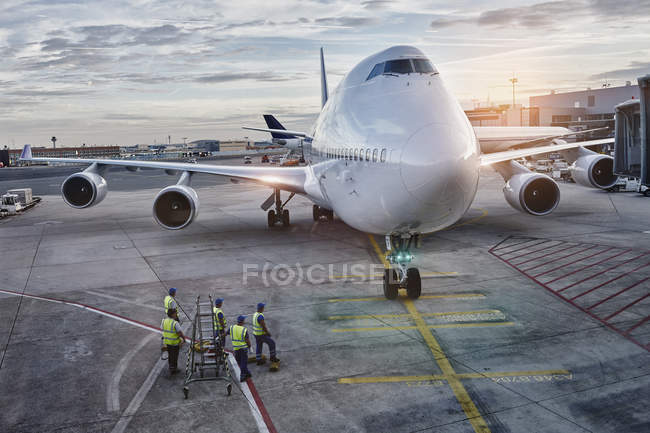 Airplane on the apron at sunset — Stock Photo