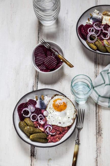 Лабскаус, ролмопы, маринованные огурцы, свекольный салат, лук и жареное яйцо — стоковое фото