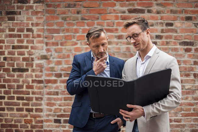Two businessmen sharing folder at brick wall — Stock Photo