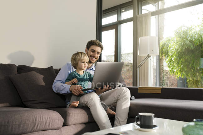 Father and son looking at laptop on couch at home — Stock Photo