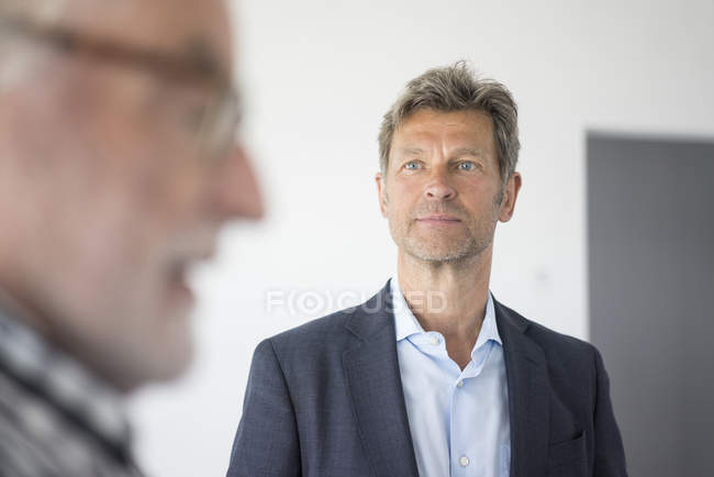 Man in suit looking at senior man talking — Photo de stock