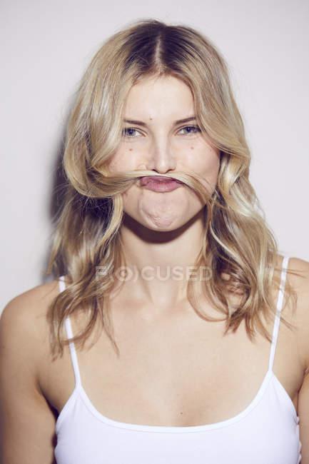 Ritratto di giovane donna tirando faccia divertente — Foto stock