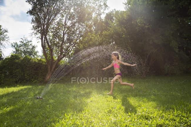 Девочка развлекается с газонным разбрызгивателем в саду — стоковое фото