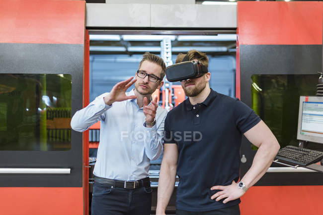 Man explaining machine to colleague wearing VR glasses in factory — Stock Photo