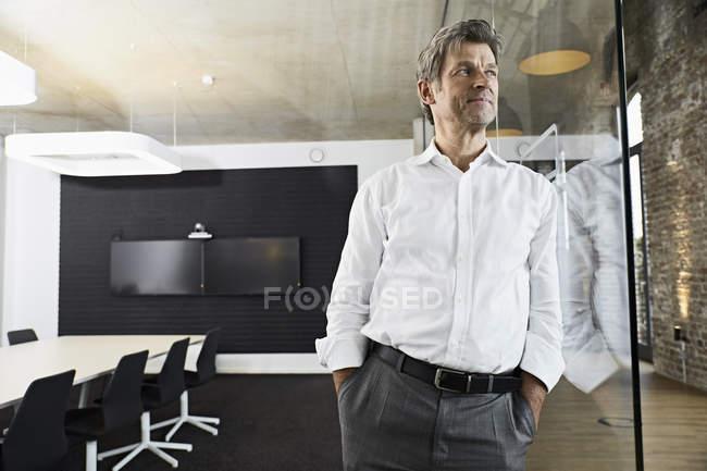 Porträt eines reifen Geschäftsmannes, der sich im modernen Konferenzraum an die Glasscheibe lehnt — Stockfoto