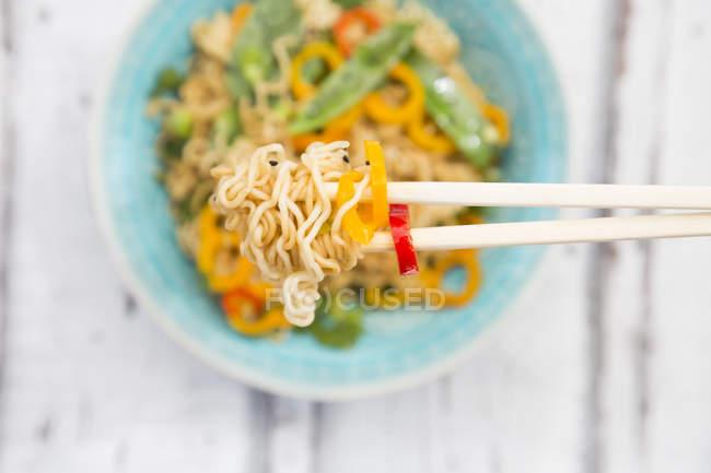 Chopsticks com macarronetes do Mie, vagem do pimentão e pimenta de sino, close-up — Fotografia de Stock