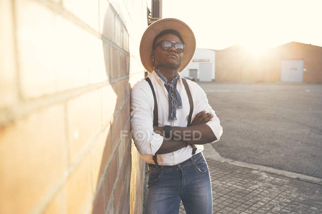 Portrait of cool young man wearing hat and sunglasses leaning against wall — Stock Photo
