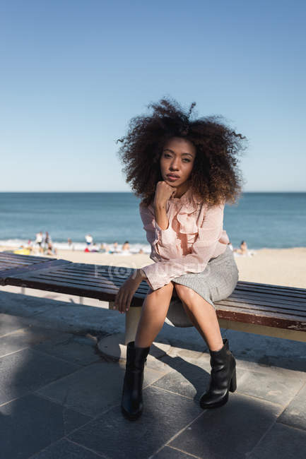 Portrait of beautiful young woman with afro hairdo sitting on a bench at the beach — Stock Photo