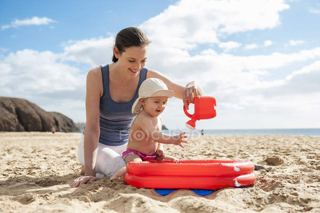 Mother playing with little daughter on the beach — Stock Photo