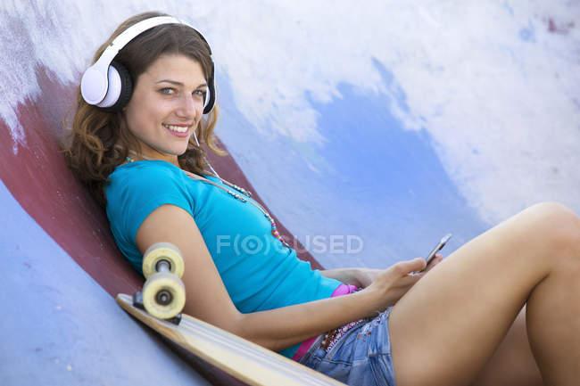 Female longboarder with earphones lying in halfpipe — Stock Photo