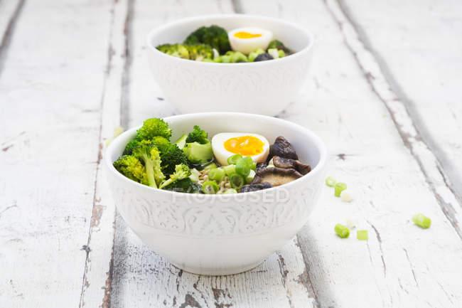 Дві чаші суп рамен з яйцем, брокколі, локшина, акапие гриби і навесні лук — стокове фото