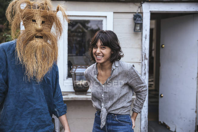 Homme utilisant le masque drôle et la femme riant — Photo de stock