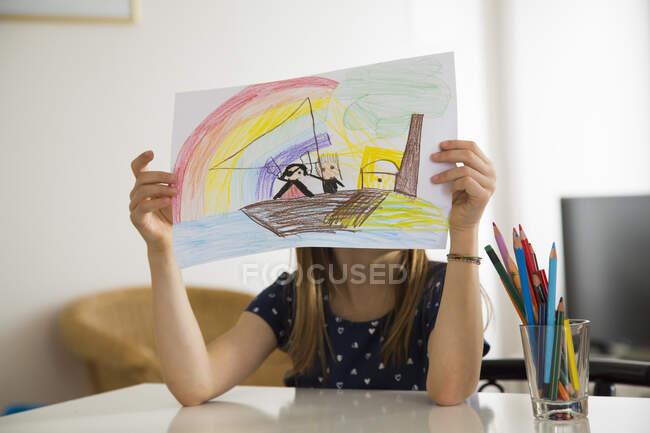 Маленька дівчинка ховається за малюнком. — стокове фото