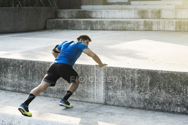 Athlete doing push-ups in city — Stock Photo