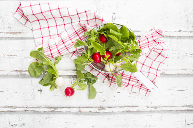 Red and white radish in strainer and kitchen towel — Stock Photo