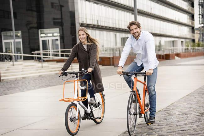Coppia sorridente in bicicletta in città — Foto stock