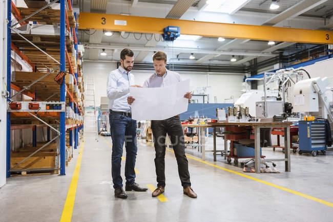 Два человека на заводе рассматривают план — стоковое фото