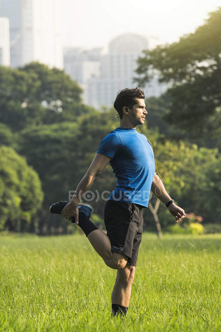 Runner warming up in urban park — Stock Photo