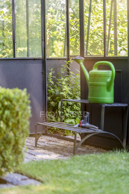 Greenhouse and green watering can — Stock Photo