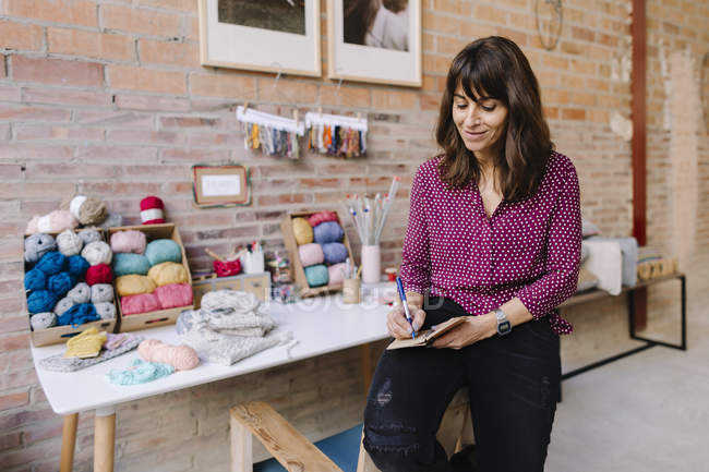 Smiling woman sitting in knitting studio and taking notes — Stock Photo