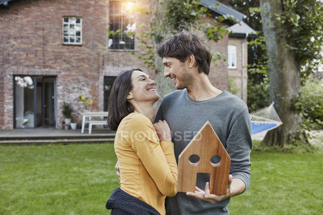Happy couple in garden of their home holding house model - foto de stock