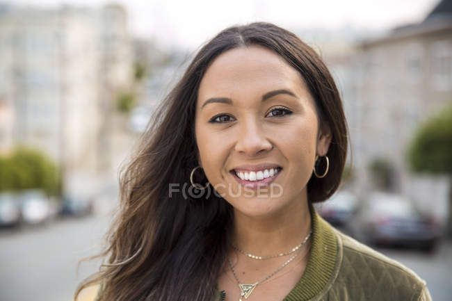 Portrait of smiling young woman on the street — Stock Photo