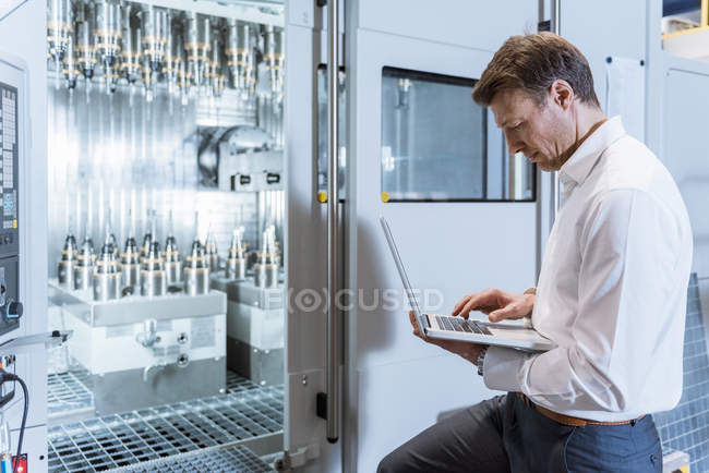 Businessman at machine in factory looking at laptop — Photo de stock