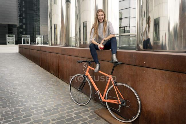 Счастливая молодая женщина с велосипедом, отдыхающая в городе, ест яблоко — стоковое фото