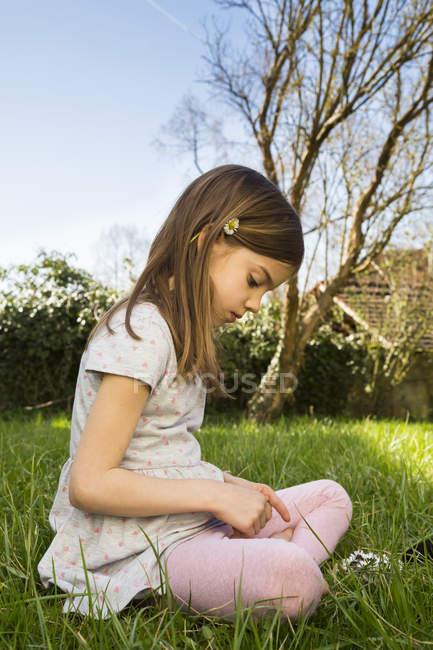 Маленька дівчинка сидить на лузі, збираючи маргаритки. — стокове фото