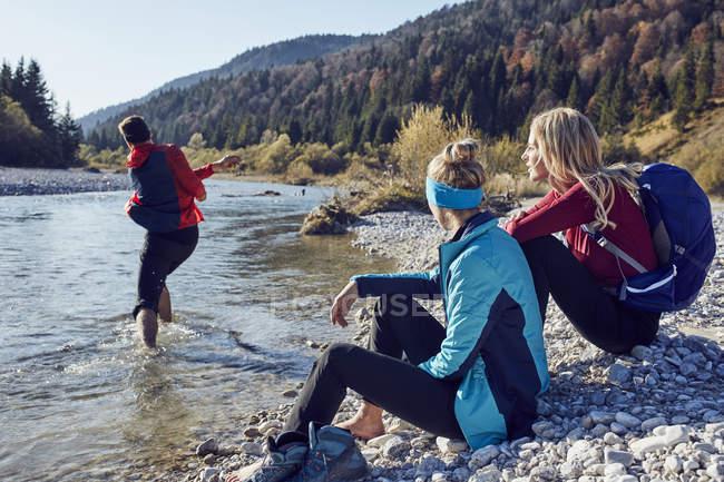 Groupe d'amis se reposant au bord de la rivière — Photo de stock