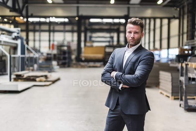 Portrait of confident businessman standing on factory shop floor — Photo de stock