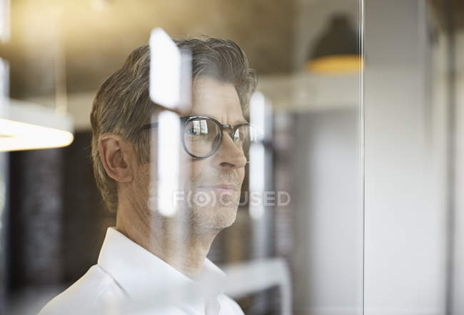 Mature businessman wearing glasses and looking out of window — Stock Photo