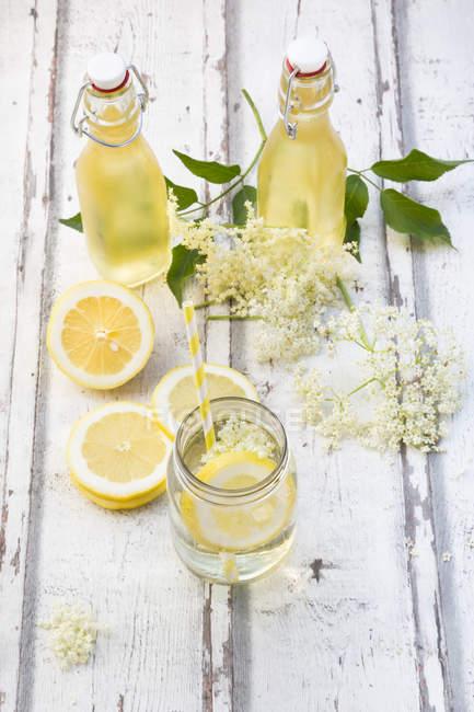 Sirope casero de flor de saúco, rodajas de limón, hojas y flores de saúco - foto de stock
