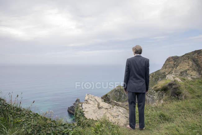 UK, Cornwall, Gwithian, businessman standing at the coast and looking at view — Stock Photo