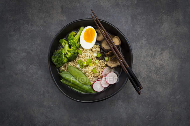 Soupe Ramen avec oeuf, pois mange-tout, brocoli, nouilles, champignons shitake et radis rouge — Photo de stock