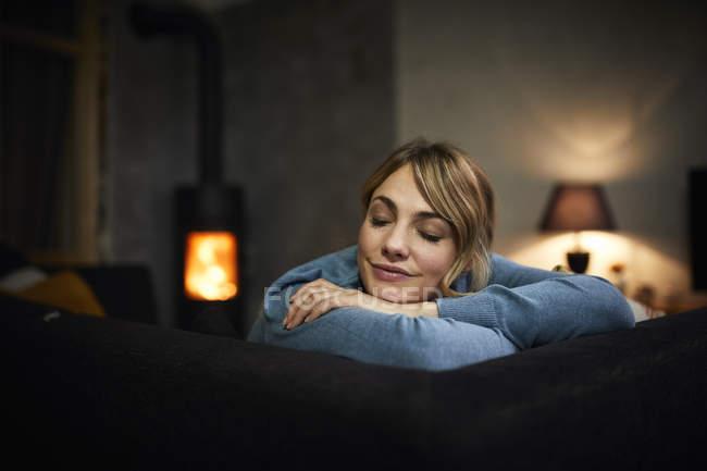 Porträt einer Frau, die es sich abends zu Hause auf der Couch gemütlich macht — Stockfoto