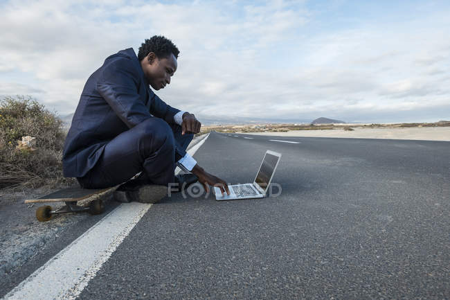 Spain, Tenerife, young businessman sitting on skateboard and using laptop — Stock Photo