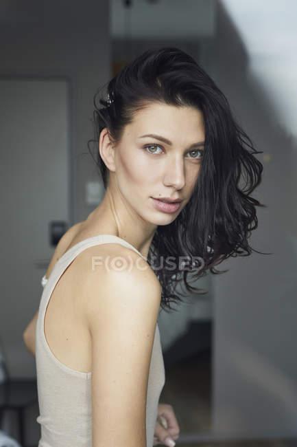 Retrato de atraente mulher jovem de cabelos escuros por trás do vidro da janela — Fotografia de Stock