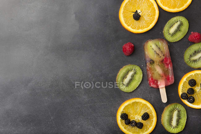 Berries, fruit slices and kiwi berry popsicle on grey background — Stock Photo