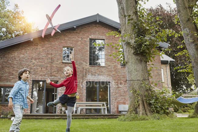 Duas crianças que jogam com o avião do brinquedo no jardim de sua home — Fotografia de Stock