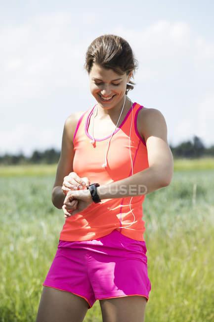 Sorridente giovane donna avendo una pausa da esercitare guardando su smartwatch — Foto stock